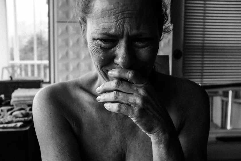 close up photography of crying woman next inside room